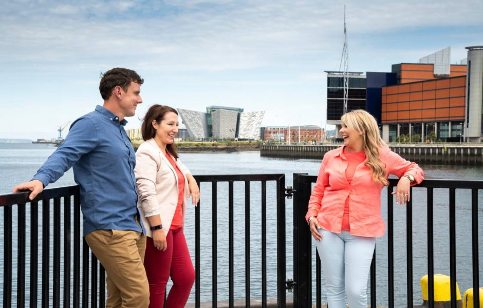 friends chatting River Lagan Belfast with Titanic in background